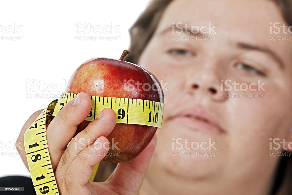 Overweight young woman considers apple wrapped in tape measure stock photo