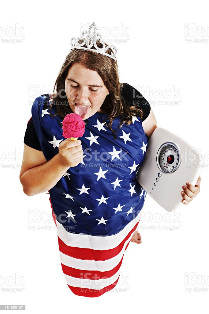 Overweight young woman dressed as Statue of Liberty licks icecream royalty-free stock photo