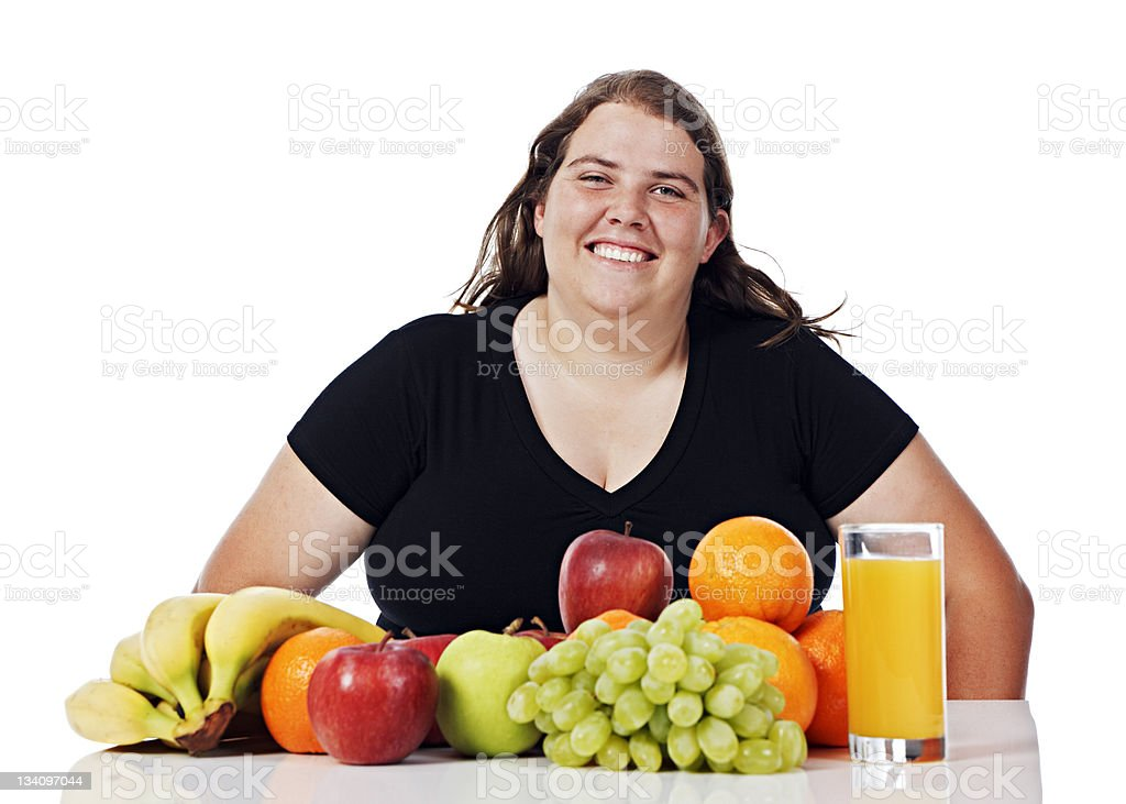 Overweight young woman happily contemplates spread of healthy food royalty-free stock photo