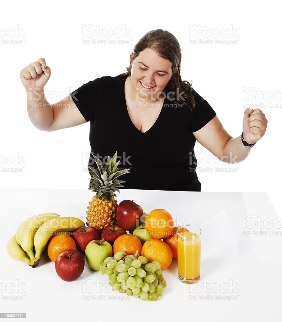 Overweight young woman looks happily at her healthy fruit choice stock photo