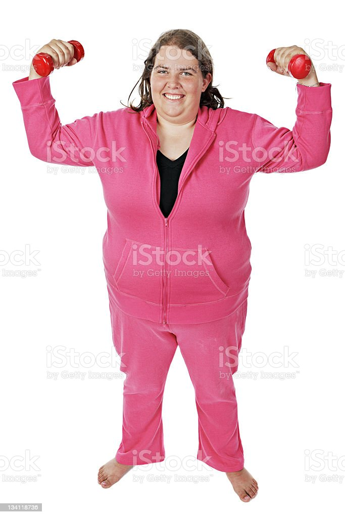 Overweight young woman smiles as she lifts weights royalty-free stock photo