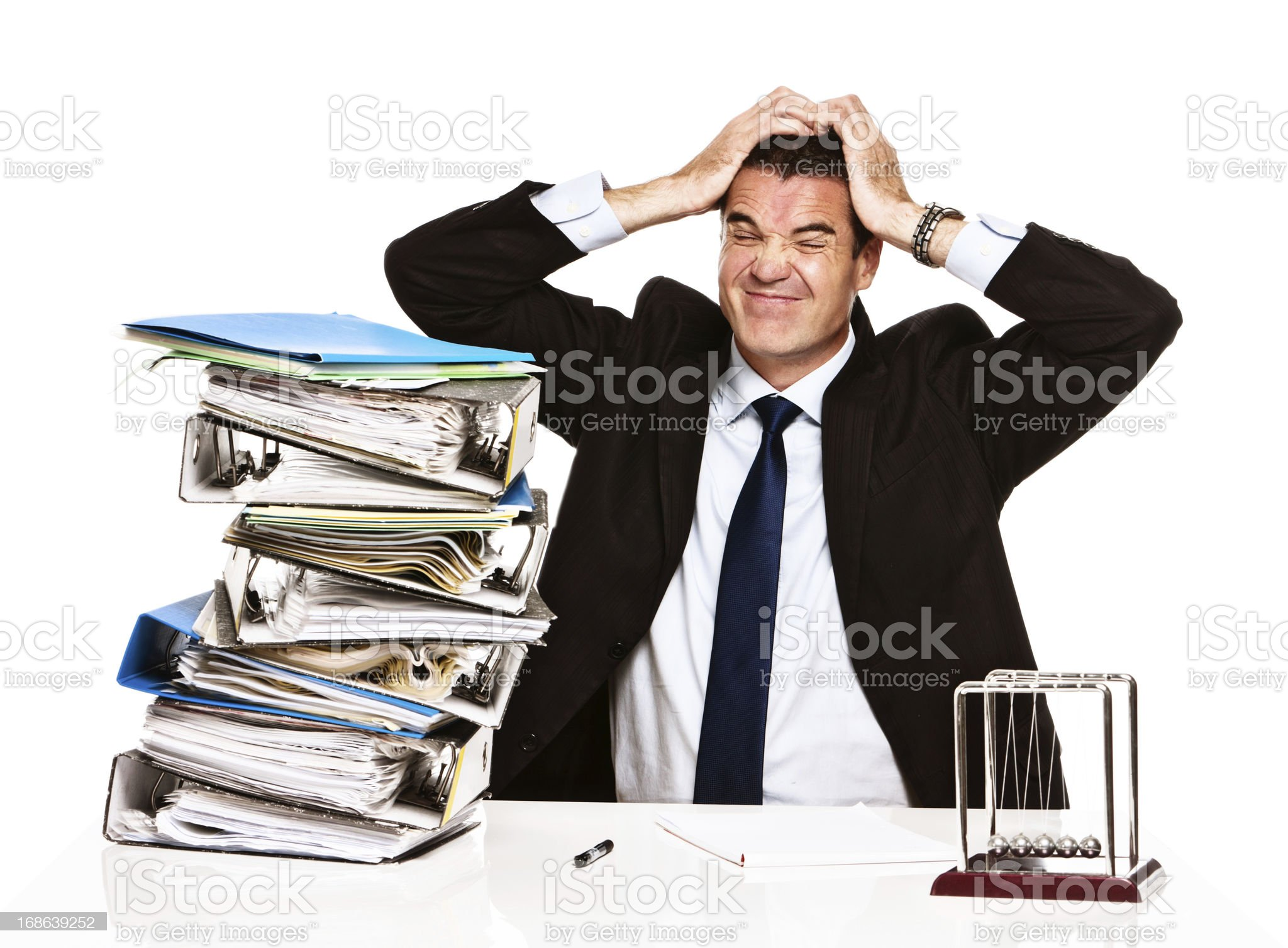 Overwhelmed businessman tears hair out in frustration over work overload royalty-free stock photo