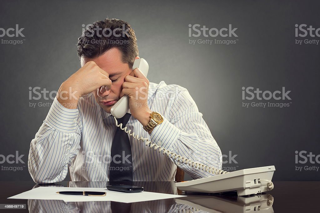 Overwhelmed  businessman with headache stock photo