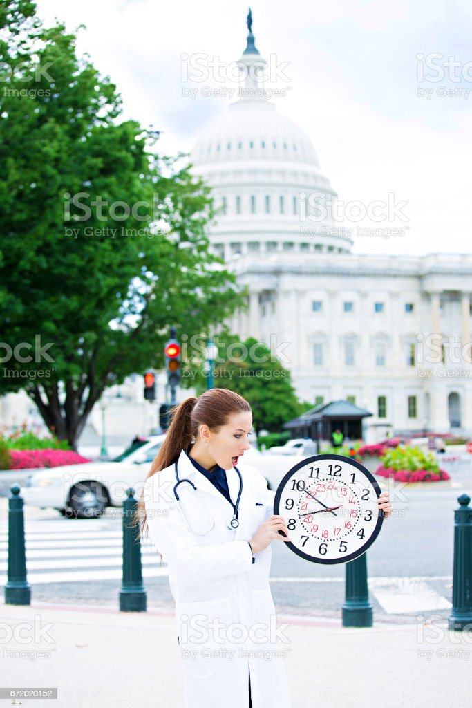 overwhelmed, busy, unhappy stressed female health care professional, woman doctor holding wall clock on streets stock photo