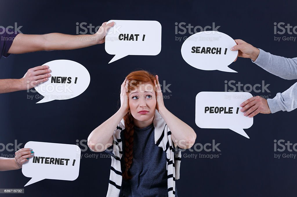 Overwhelmed woman and speech bubbles stock photo