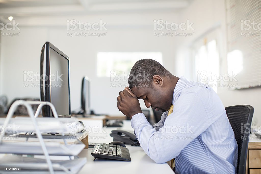 Overworked african businessman sitting at his desk. stock photo