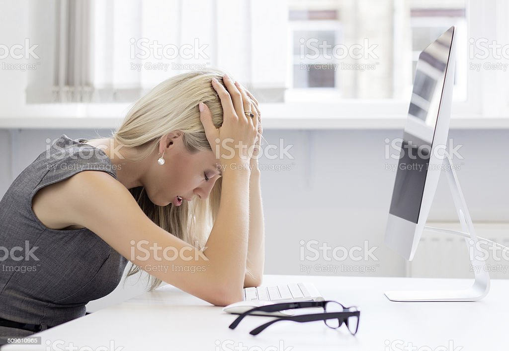 Overworked and frustrated young woman in front of computer stock photo