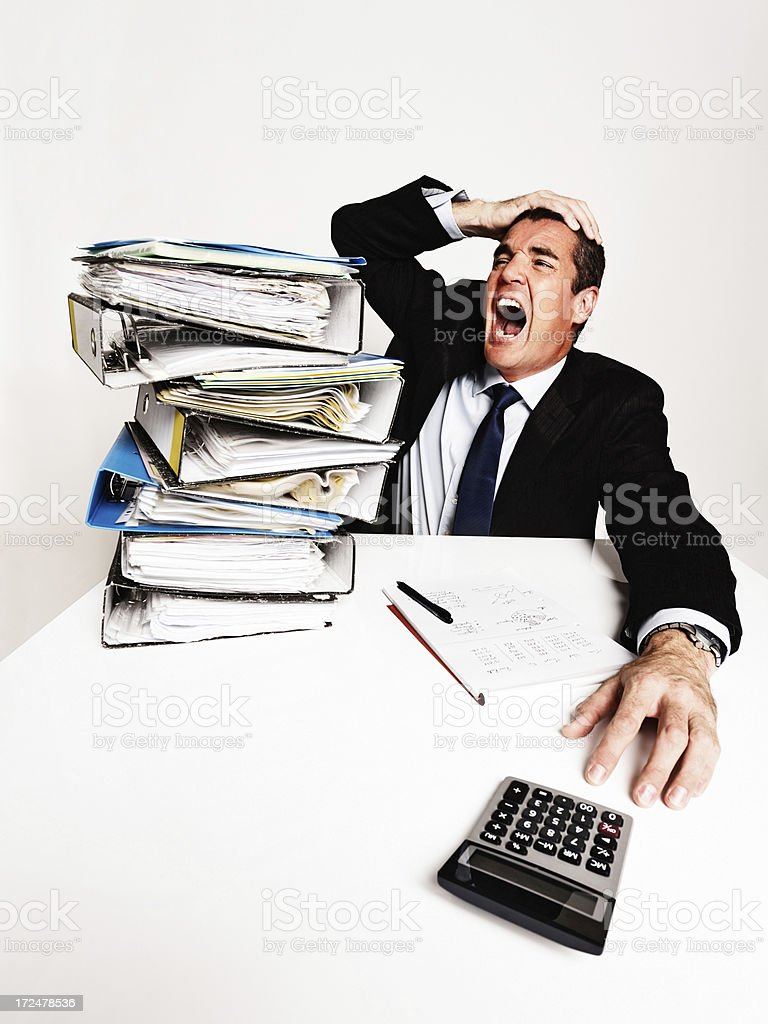 Overworked and overwhelmed businessman yells in frustrated despair royalty-free stock photo