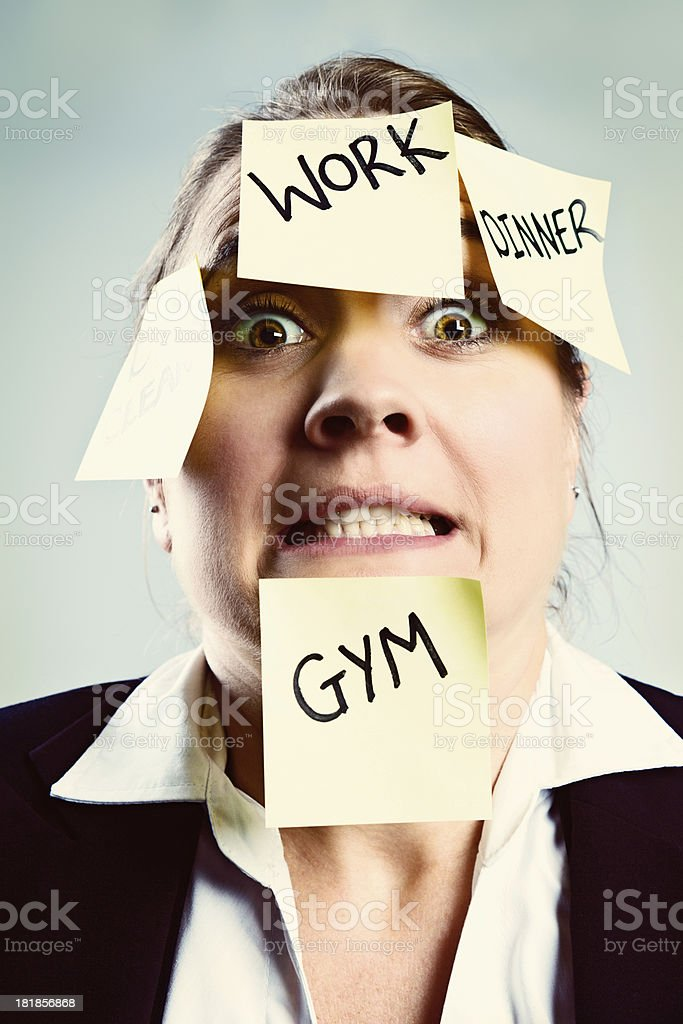 Overworked and overwrought woman covered in sticky task reminders royalty-free stock photo