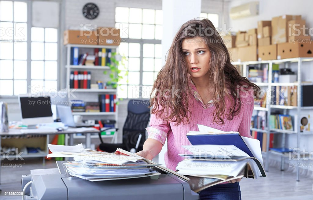 Overworked assistant using copy machine at the office stock photo