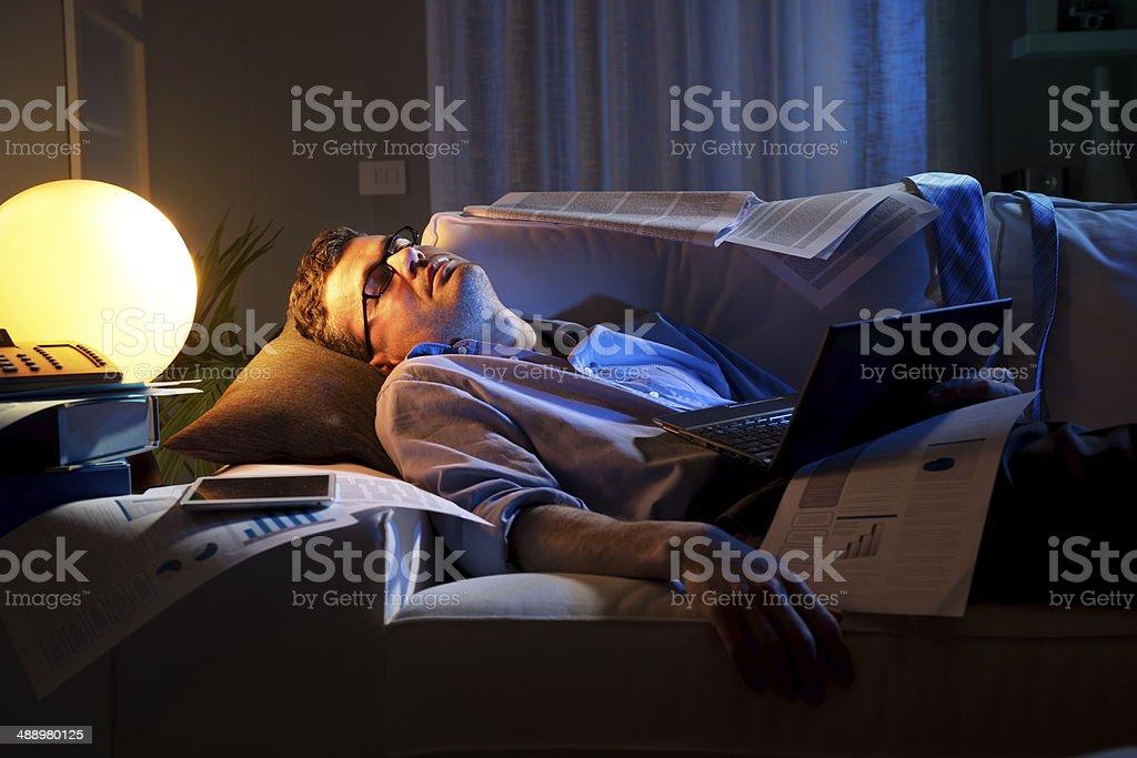 Overworked businessman on sofa stock photo