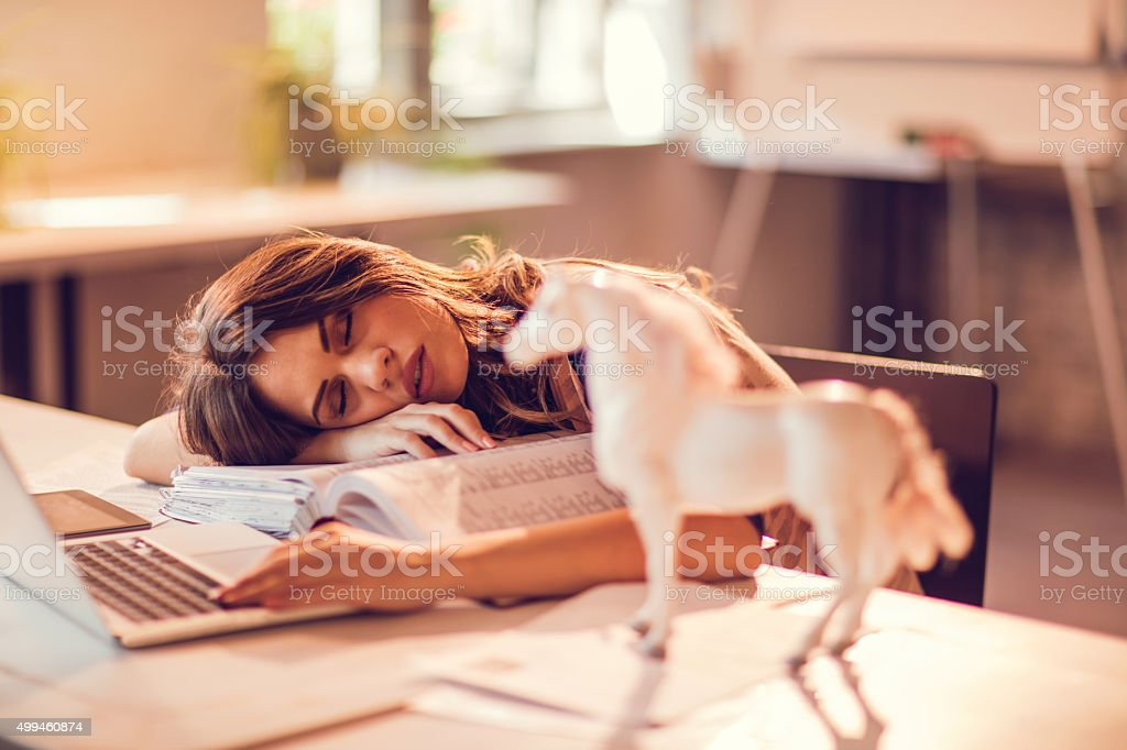 Overworked businesswoman taking a nap on a bunch of paperwork. stock photo