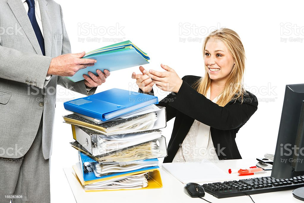 Overworked but smiling businesswoman accepts even more work from boss royalty-free stock photo