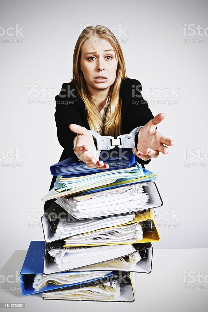 Overworked handcuffed young businesswoman is a slave to her job royalty-free stock photo