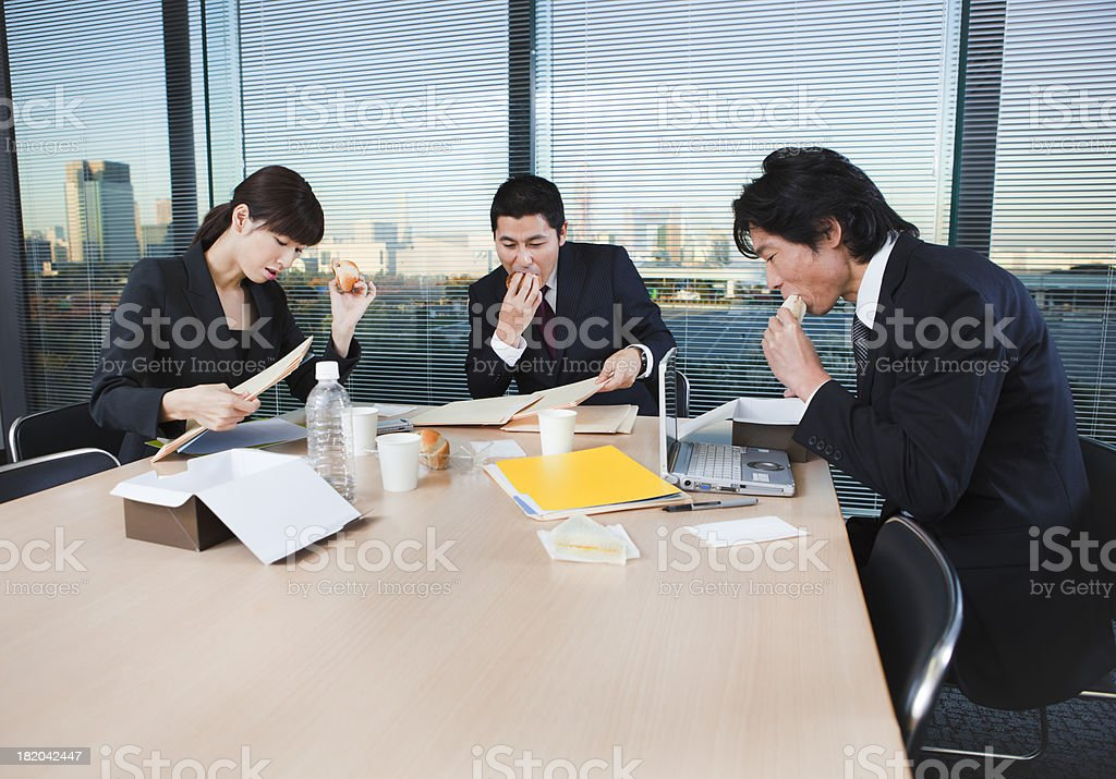 Overworked Japanese Office Workers Working Through Lunch stock photo