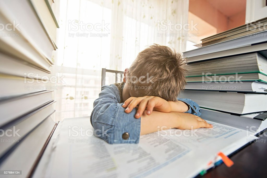 Overworked little boy trying to learn too much stock photo