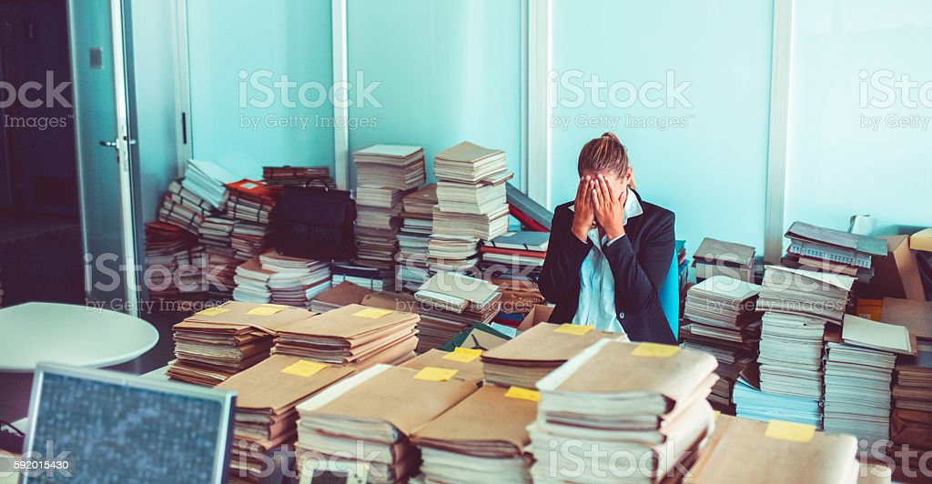 Overworked office worker, bureaucracy, archives stock photo
