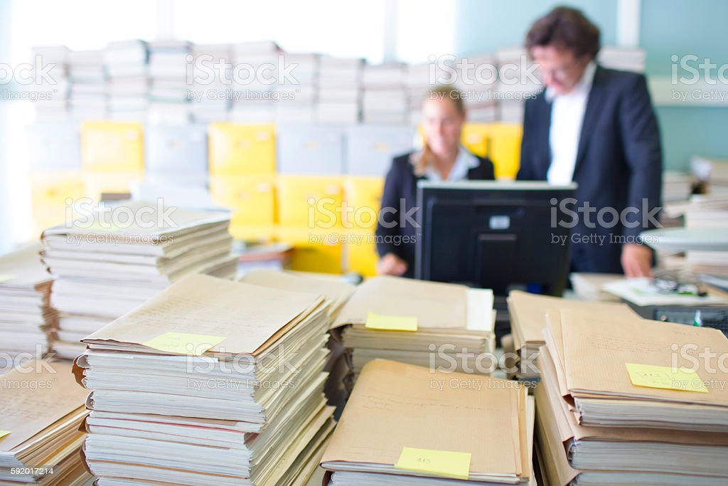 Overworked office workers, bureaucracy, archives stock photo