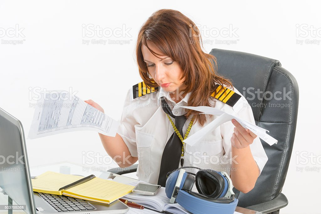 Overworked woman airline pilot in the office stock photo