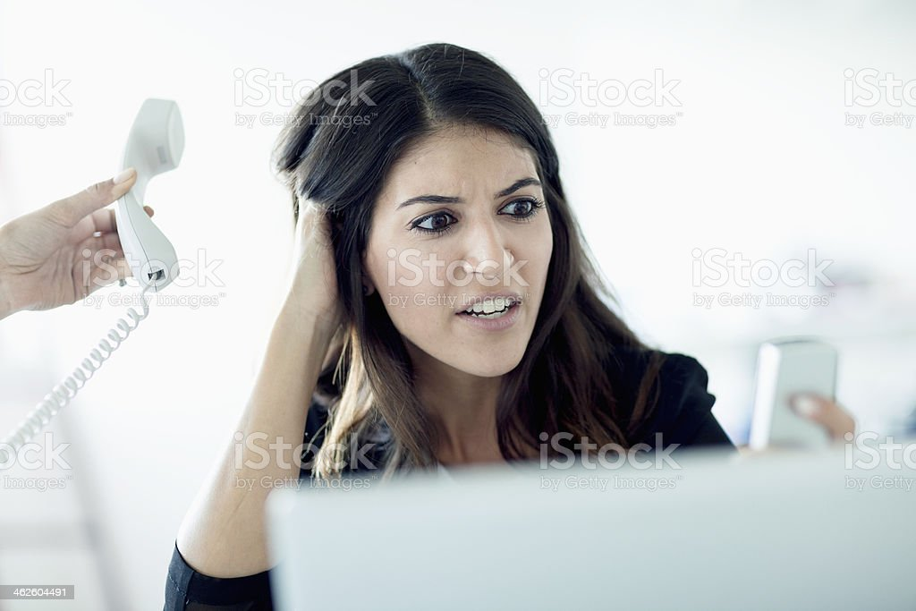 Overworked young businesswoman answering phones stock photo
