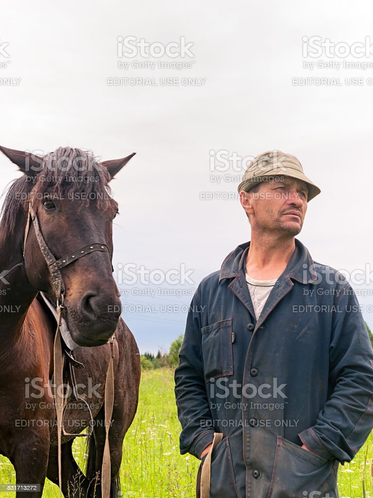 Сowboy stands near bay horse stock photo