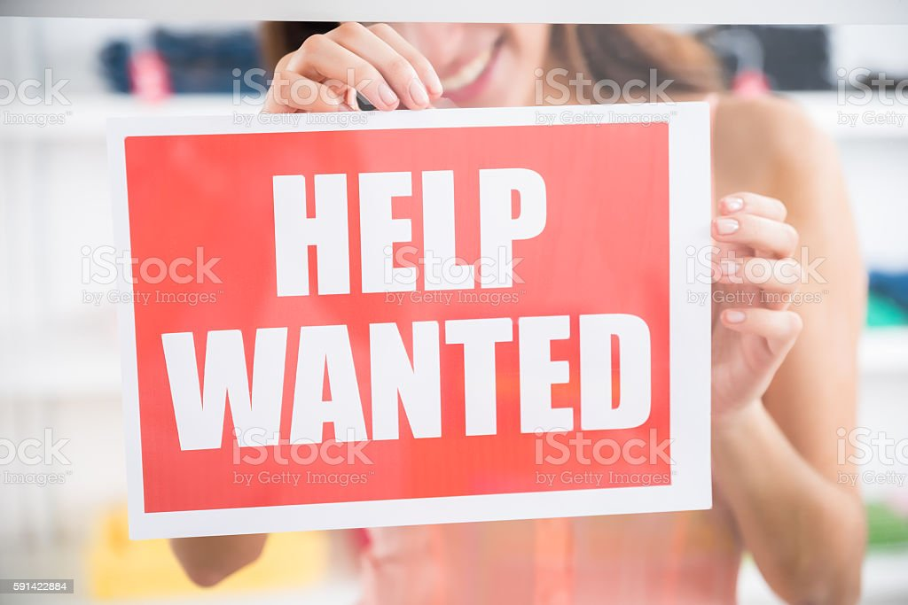 Owner Holding Help Wanted Sign In Retail Store stock photo