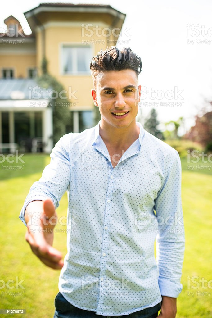 Owner in front of his villa showing it stock photo