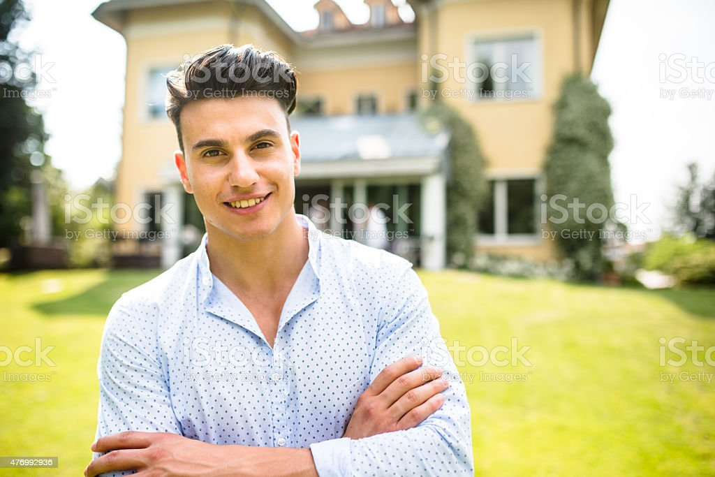 Owner in front of his villa with arm crossed stock photo