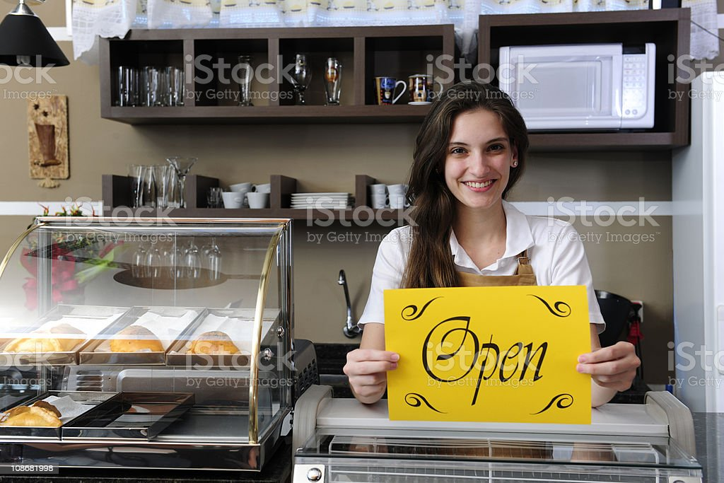 owner of a cafe showing open sign stock photo