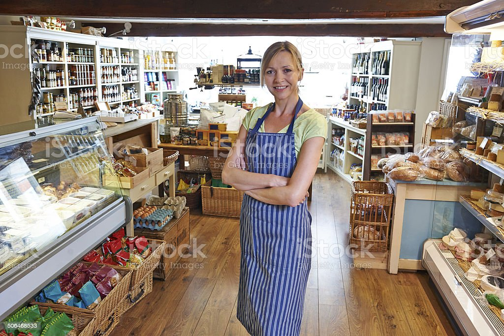 Owner Of Delicatessen Standing In Shop stock photo