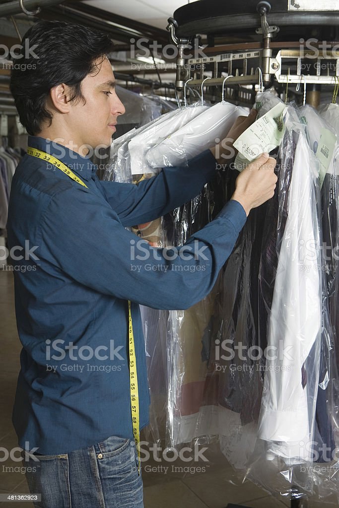 Owner Organising Clothes On Rail In Laundry stock photo