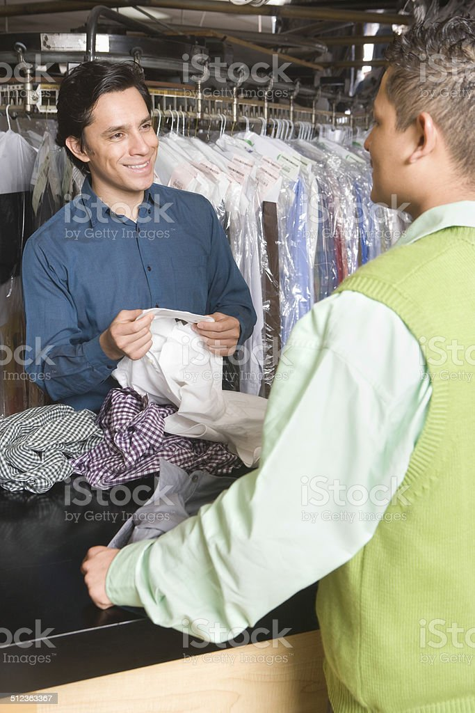 Owner Showing Dry Cleaned Shirts To Customer At Counter stock photo
