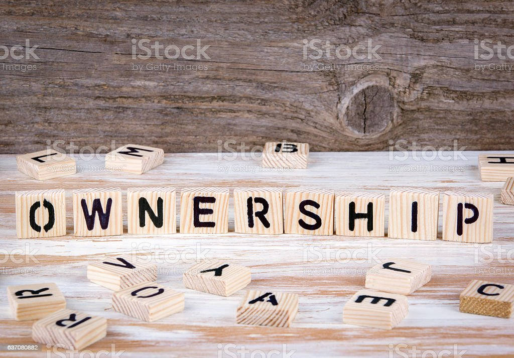 Ownership from wooden letters stock photo