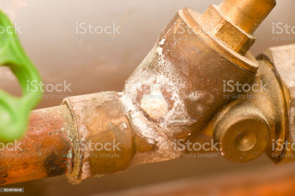 Oxidized old water pipe with shut-off valve stock photo