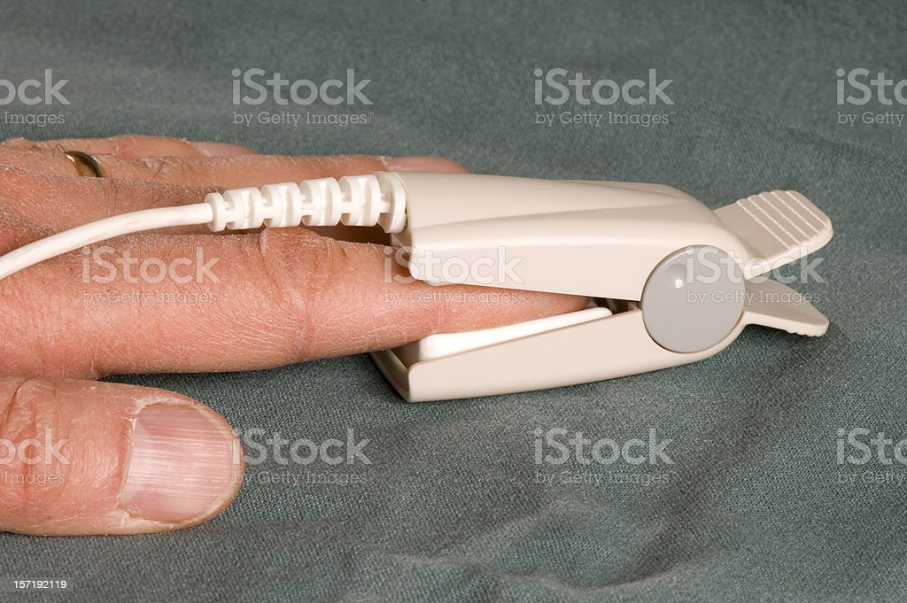 Oximeter sensor on a patient's finger royalty-free stock photo