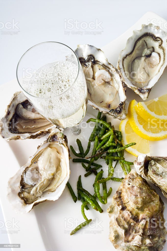 Oysters, lemon, seaweed, champagne glass on plate stock photo