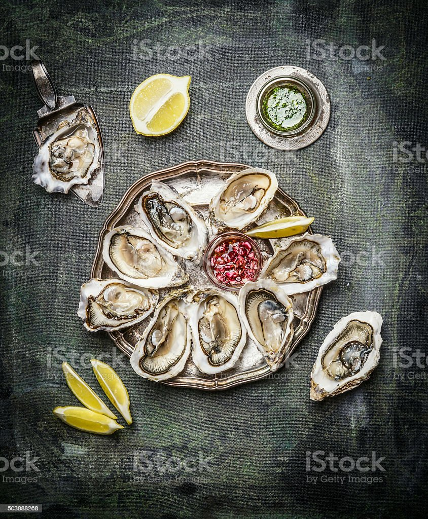 Oysters plate with lemon and sauces , top view stock photo