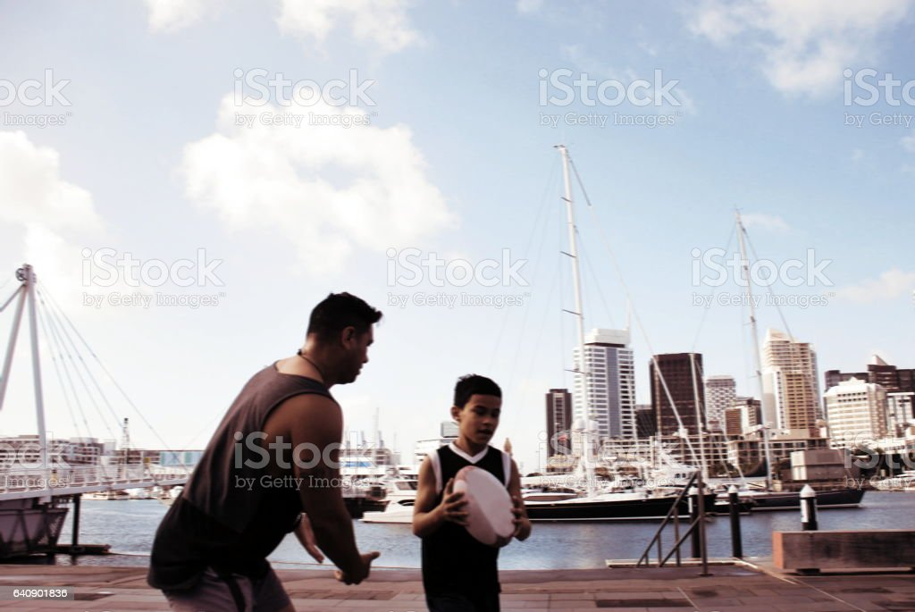 Pacific Island Man and Boy Plays Rugby against a Cityscape Harbour, in Blurred Motion stock photo