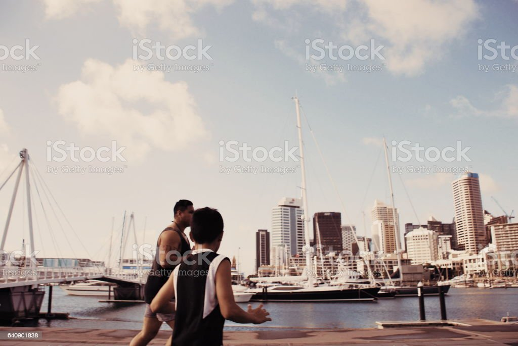 Pacific Island Man and Boy Plays Rugby against a Cityscape Harbour stock photo