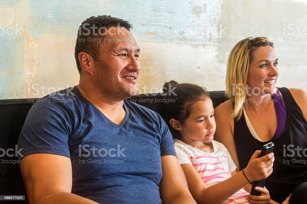 Pacific Islander Mixed Race Maori Family Watching Television Together stock photo
