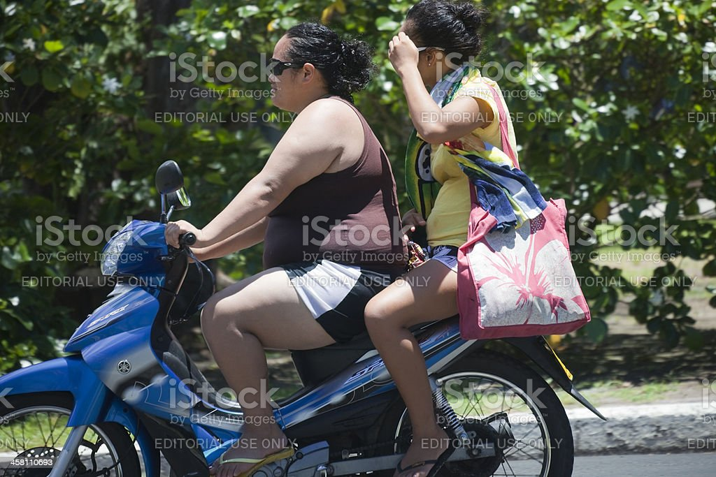 Pacific Islander women riding Yamaha Spark motorbike royalty-free stock photo