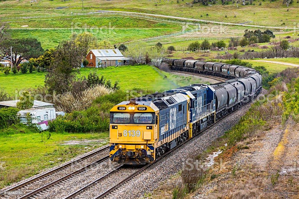 Pacific National bulk grain train rounding bend in rural landscape stock photo