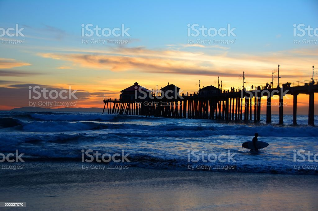 Pacific Ocean Surfer Exiting At Dusk stock photo