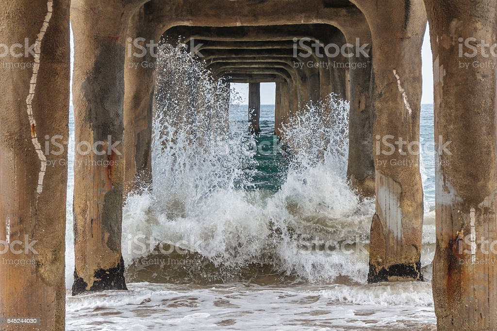 Pacific Ocean Waves Crashing on the Pilings of Concrete Pier stock photo