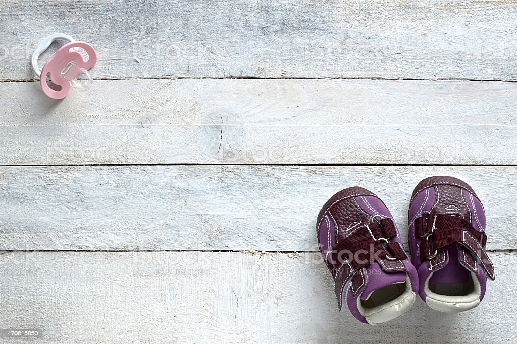 Pacifier, and baby shoes on white wood stock photo