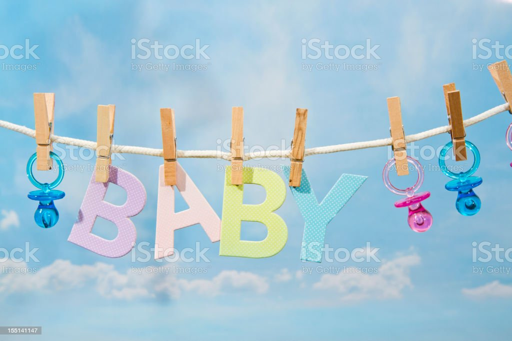 Pacifiers and BABY Letters Hanging On A Clothesline stock photo