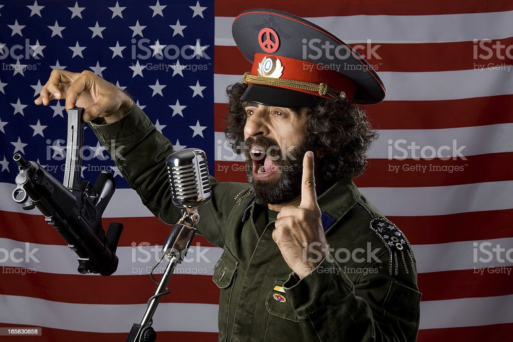 Pacifist in military uniform leaving his weapon before American flag royalty-free stock photo