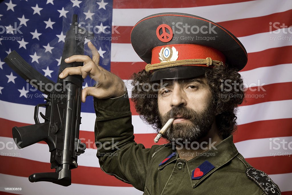 Pacifist in military uniform leaving his weapon before American flag stock photo