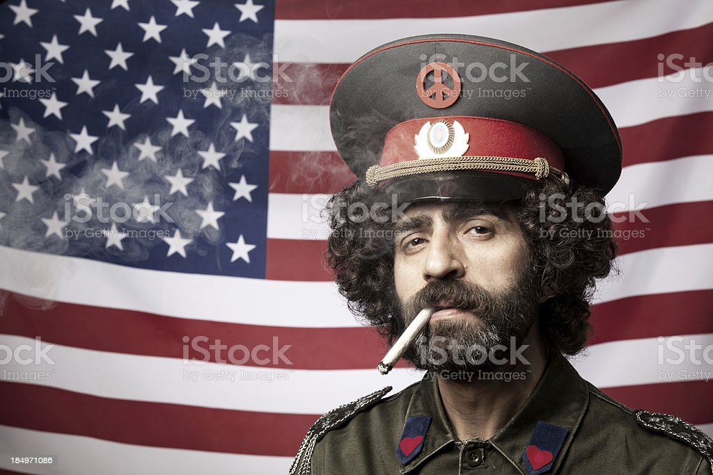 Pacifist in military uniform smoking before American flag stock photo