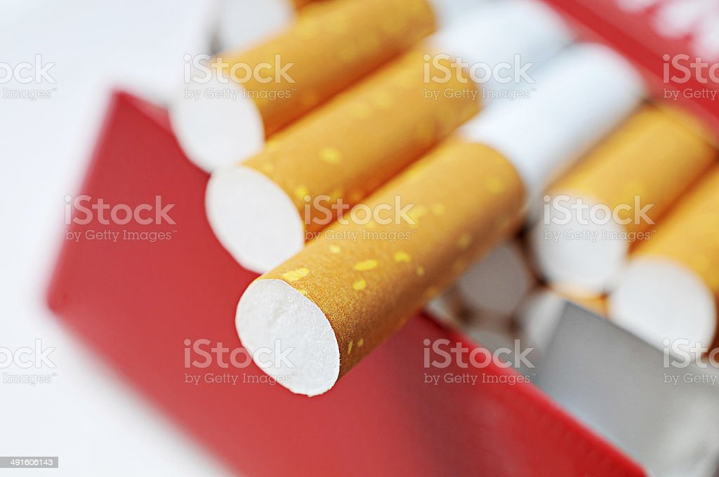 Pack of cigarettes in red box with filters in focus stock photo